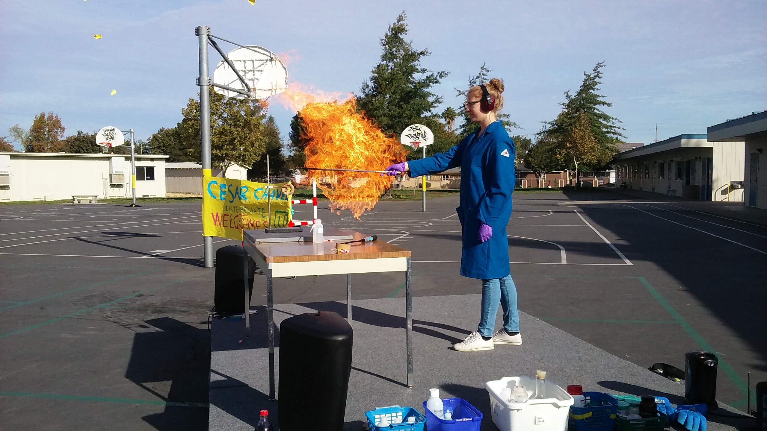 Sommer demonstrates propane combustion at an outreach event at an elementary school by triggering an explosion a propane-filled balloon with just a small flame.